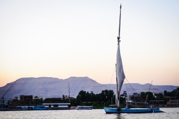 A man climbing to the top of his sail on the Nile.
